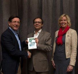 Wim Schellekens (links) overhandigt Frank de Grave (midden) het boek 'Zorg op zijn best'. Rechts uitgever Monique Scholten Theessink.
