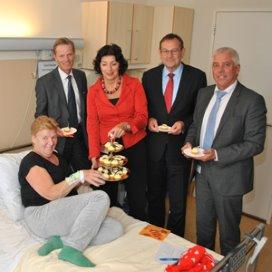 Alle patiënten en cliënten krijgen vandaag een gebakje om de fusie te vieren. Mevrouw Schmidt uit Leiden kreeg het eerste gebakje uitgereikt door de raad van bestuur.