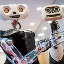 De zelflerende zorgrobot Lea (L) en Robbie houdt een beker vast tijdens een demonstratie bij de TU Delft. In Delft wordt gewerkt aan betaalbare personal robots voor zorg- en huishoudelijke taken.