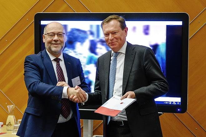 Willy Spaan, voorzitter van de Nederlandse Federatie van Universitair Medische Centra, overhandigt het plan 'Onderzoek & Innovatie met en voor de gezonde regio'aan minister Bruins van Medische zorg