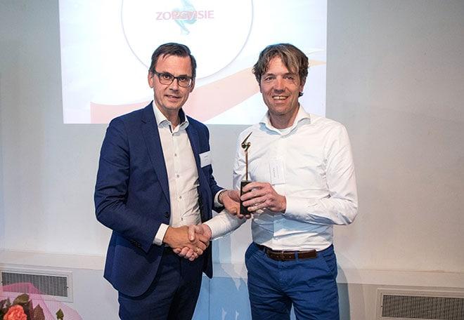 Juryvoorzitter Andrë Rouvoet feliciteert Zorgmanager van het Jaar 2019 Peter de Visser