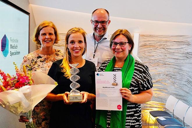 Arts-onderzoeker Marin de Jong (midden) met de Wetenschaps- en Innovatieprijs voor de door haar onderzochte MijnIBDCoach.